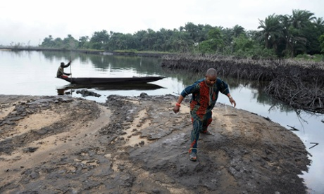 A man walks on slippery spilled crude oil on the shores and in the waters of the Niger Delta swamps of Bodo.