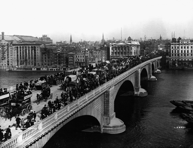 Traffic on London Bridge over the river Thames in 1904. The bridge is full of pedestrians, horse drawn omnibuses and horse drawn carriages. Various wharfs and warehouses are visible on the left of the shot across the river.