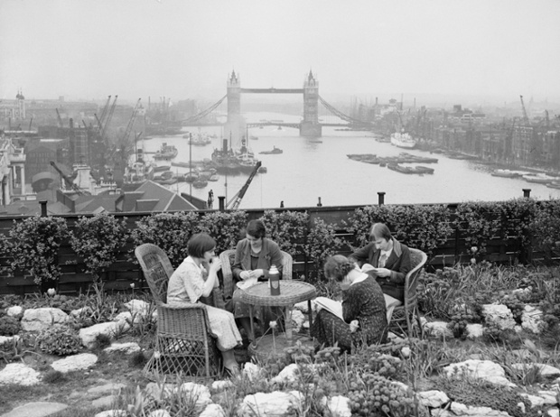 Four women have lunch in the roof garden on Adelaide House, overlooking the River Thames and Tower Bridge, circa 1934.