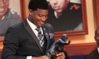 Florida State quarterback Jameis Winston looks at the Heisman Trophy