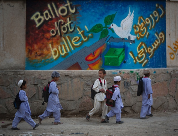 Schoolchildren walk past election graffiti on their way home on the outskirts of Kandahar