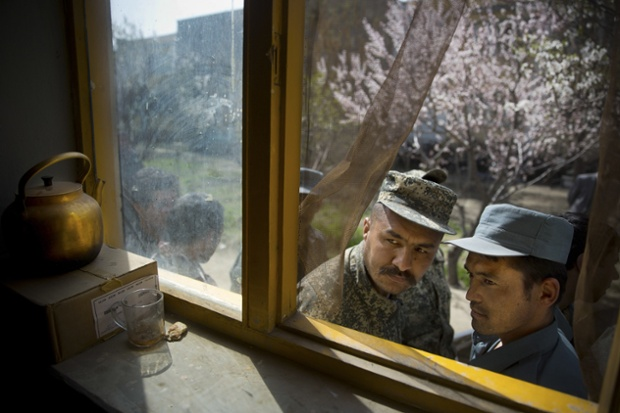 An Afghan soldier and a police officer peek through a window as they queue outside a school in Kabul on the last day of voter registration for the elections