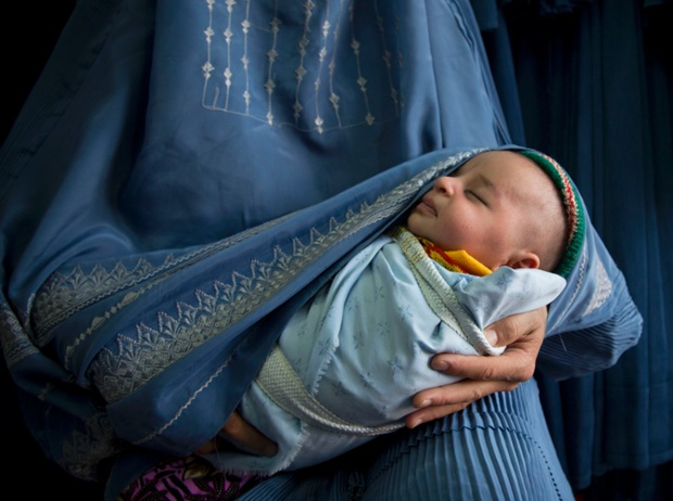 A woman holds her baby in April 2013 as she waits to try on a new burqa in a shop in the old town of Kabul