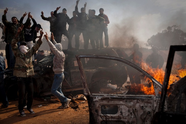 Libyan rebels celebrate next to burning cars after leader Muammar Gaddafi's forces are pushed back from Benghazi in March 2011
