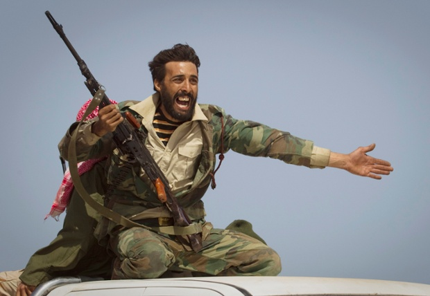 A Libyan rebel urges people to flee as Gaddafi's forces start shelling the frontline outside Bin Jawaad