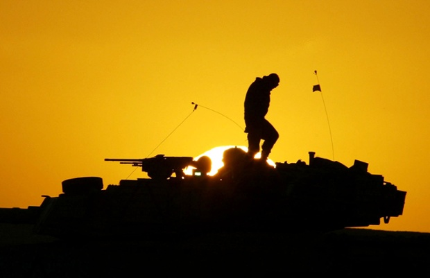A US soldier walks on top of his armoured vehicle at sunset as he prepares for a night military exercise in the Kuwaiti desert south of the Iraq border in December 2002
