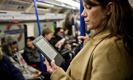 Woman reading Kindle on the tube
