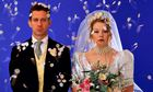 Unhappy bride and groom frowning under confetti