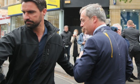 Nigel Farage is lead back to his car after after being hit with an egg thrown by a man who gave his name as Fred, an unemplyed musician.