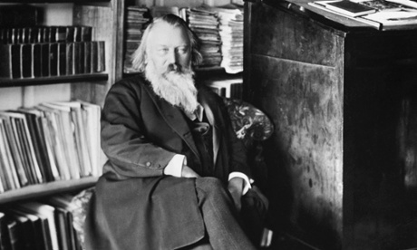 Johannes Brahms seated in his study, with his work desk at the right.