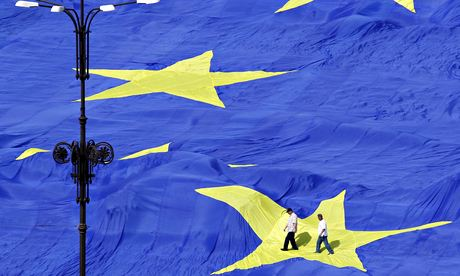 Two men walking in the middle of a star on a huge EU flag