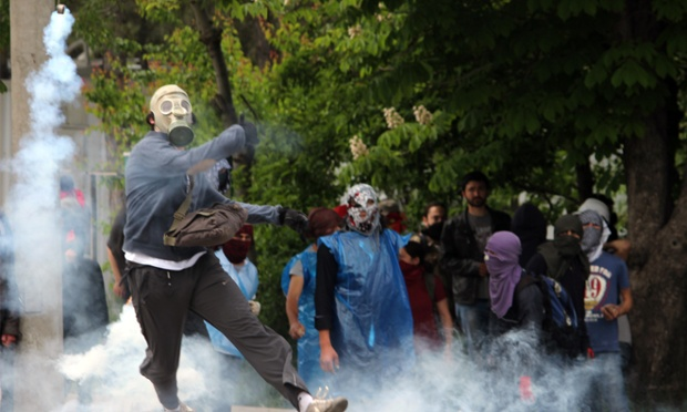 A masked protester hurls a stone at the riot police during the clashes in Ankara following a protest against the government and Soma Holdings