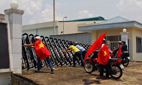 Protesters holding Vietnamese flags attempt to push down the gate of a factory in Bien Hoa