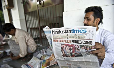 A Delhi resident reads a newspaper with the BJP's election victory on the front