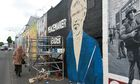 A mural of Gerry Adams is painted as detectives question Sinn Féin leader over McConville murder