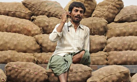 A labourer speaks on his mobile phone as he sits on onion sacks Siliguri, India