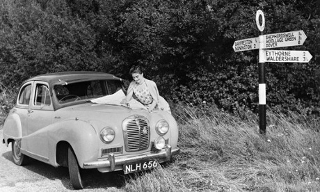 Leaning on the bonnet of her Austin car by a countryside signpost a woman driver studies a map, circa 1960