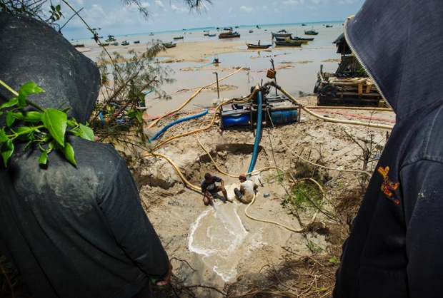 Workers wearing hoods look on as two men work in a small pit to look for tin on Rebo  beach on the Indonesian island of Bangka.