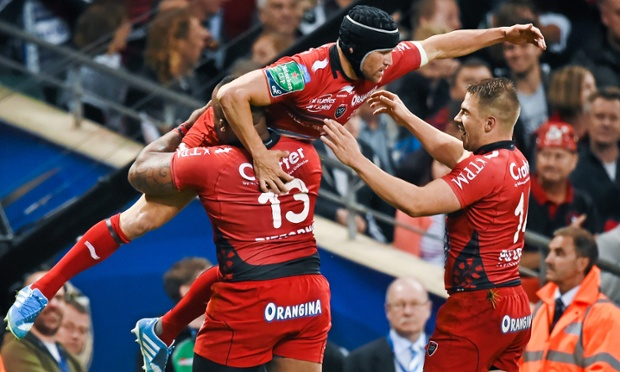 Matt Giteau, top, is congratulated by his Toulon team-mates after scoring a try.
