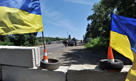 Ukrainian army soldiers stand guard at a checkpoint on the road between Izyum to Slavyansk