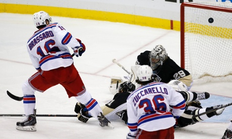 New York Rangers' Derick Brassard puts the puck past Pittsburgh Penguins goalie Marc-Andre Fleury  and Robert Bortuzzo for the game-winning goal in the first overtime period of Game 1 of a second-round NHL hockey playoff series in Pittsburgh, Friday, May 2, 2014.