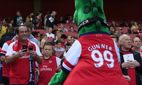 An Arsenal fan takes pictures of moscot Gunnersaurus ahead of the match.