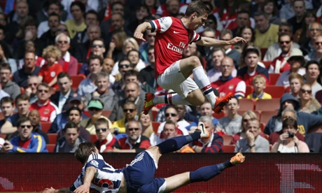 Nacho Monreal leaps over the tackle from West Bromwich Albion's Craig Dawson.