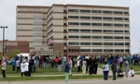 People wait outside a Veterans Affairs hospital after they were evacuated,