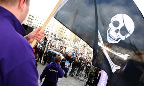 Man waves a skull and crossbones flag at an outdoor gathering