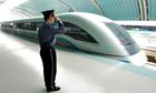 A Chinese policeman salutes as a magnetic-levitation train leaves Shanghai.