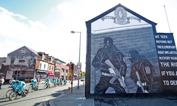 Riders of Astana team cycle past murals in east Belfast before the Giro d'Italia.