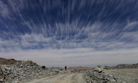 A man walks down a dirt road in the Atacama Desert. Despite being one of the most inhospitable places on earth, the Atacama is still mined: in 2010 this made world-wide news, when the Copiapó mining accident led to the dramatic rescue of 33 trapped miners (AP Photo/Dario Lopez-Mills). Photograph: Dario Lopez-Mills/AP