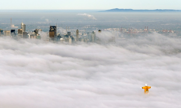 In this photo released by sportsbet.com.au, a hot air balloon in the likeness of Brazil's Christ The Redeemer statute, wearing the colors of Australia's soccer team, floats through clouds over the Melbourne skyline.