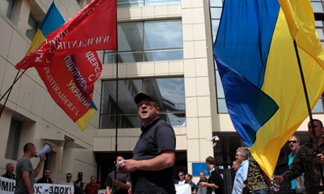 Ukrainian protesters hold banners outside the tax ministry in Kiev on 23 May 2014.