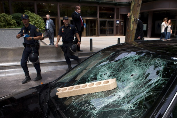 Police officers look at a a car that was damaged by demonstrators after it was suspected to be a private taxi in Madrid, Spain.