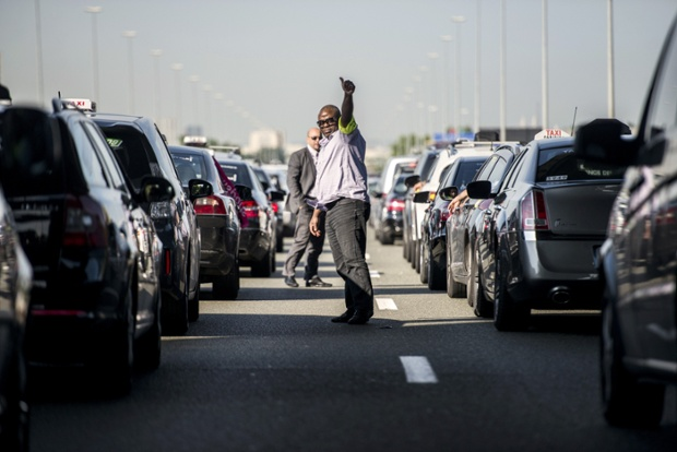 Taxi drivers block a road near Roissy outside Paris as they take part in a demonstration to protest against the growing number of minicabs or Voitures de Tourisme avec Chauffeurs (VTC).