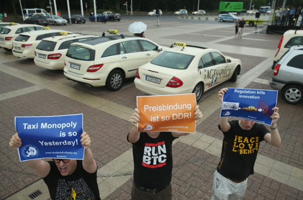 Supporters of online ride-sharing apps hold up signs demanding an end to the taxi monopoly at a demonstration by taxi drivers in Berlin, Germany.