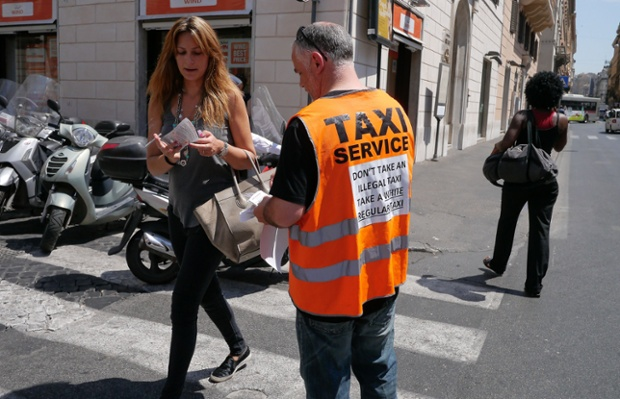 An Italian taxi driver distributes leaflets reading