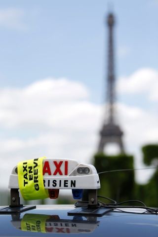 A taxi sign is partially covered as Parisian taxi drivers demonstrate near the Eiffel tower in Paris, France.