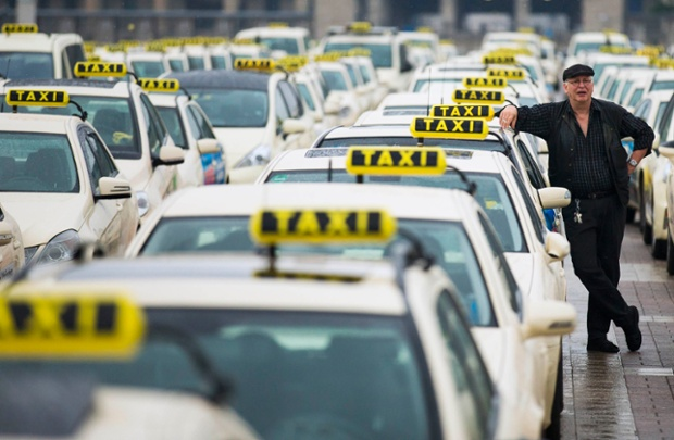 A taxi driver listens to speeches by his colleagues in front of the Olympic stadium in Berlin, Germany.