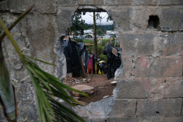 A hole in a wall for people to access the Squatters camp less than a mile from the Itaquerão World Cup Stadium in a district of Sao Paolo in Brazil.