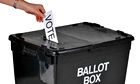 Hand with bracelet and nail-polished fingers putting vote in ballot box