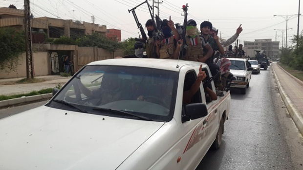 Fighters of the Islamic State of Iraq and the Levant (Isis) celebrate on vehicles taken from Iraqi security forces in Mosul