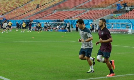 Alex Oxlade-Chamberlain runs with an England coach at the Arena da Amazonia in Manaus.