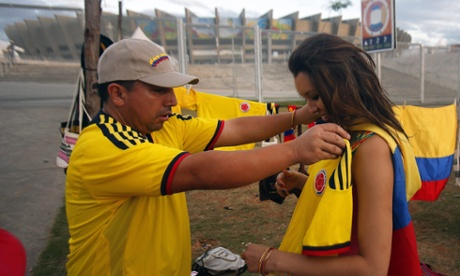 A Colombia fan, right, buys a shirt outside Estádio Mineirão in Belo Horizonte, before the game with Greece.