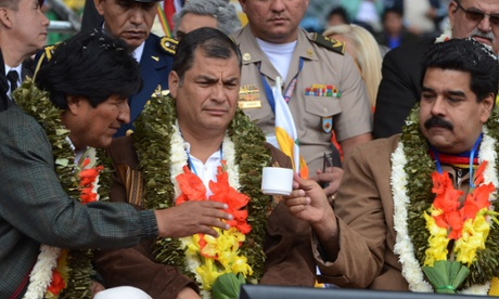 Bolivia's President Evo Morales, left, hands a cup of tea to Venezuela's Prsident Nicolas Maduro, right, as Ecuador's President Rafael Correa, center, looks on during the welcoming ceremony for delegates of the G77 + China Summit in Santa Cruz, Bolivia.