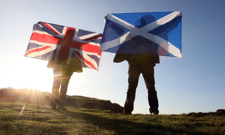 Scottish and British flags held up over Edinburgh, Scotland