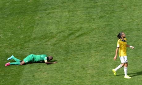 Ivory Coast's midfielder Yaya Toure hits the ground whilst Colombia's defender and captain Mario Alberto Yepes walks away.
