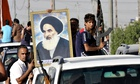 Iraqi Shia volunteers  carry a portrait of Ayatollah Ali al-Sistani
