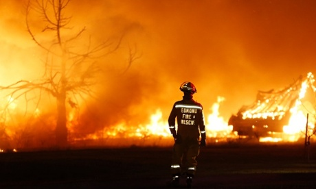 An Edmond firefighter looks at a fire raging in a mobile home park in Oklahoma on Sunday. Wildfires have become more prevalent in the US because of climate change.